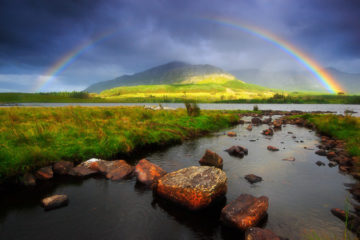 A rainbow forms as a shaft of sunlight hits the spray, raised by the wind, over Ben Baun at Lough Inagh in Connemara.