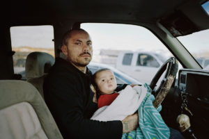 Richard, a Tattoo Artist, with his son in front of the only Gas-Station in Hays. Hays is a small community with around 800 people near the reservation's southern end. People come here often as it is the only place to get a little snack or soda without driving a lot further off the Reservation to the next grocery store. Richard is also a very successful bow-hunter.